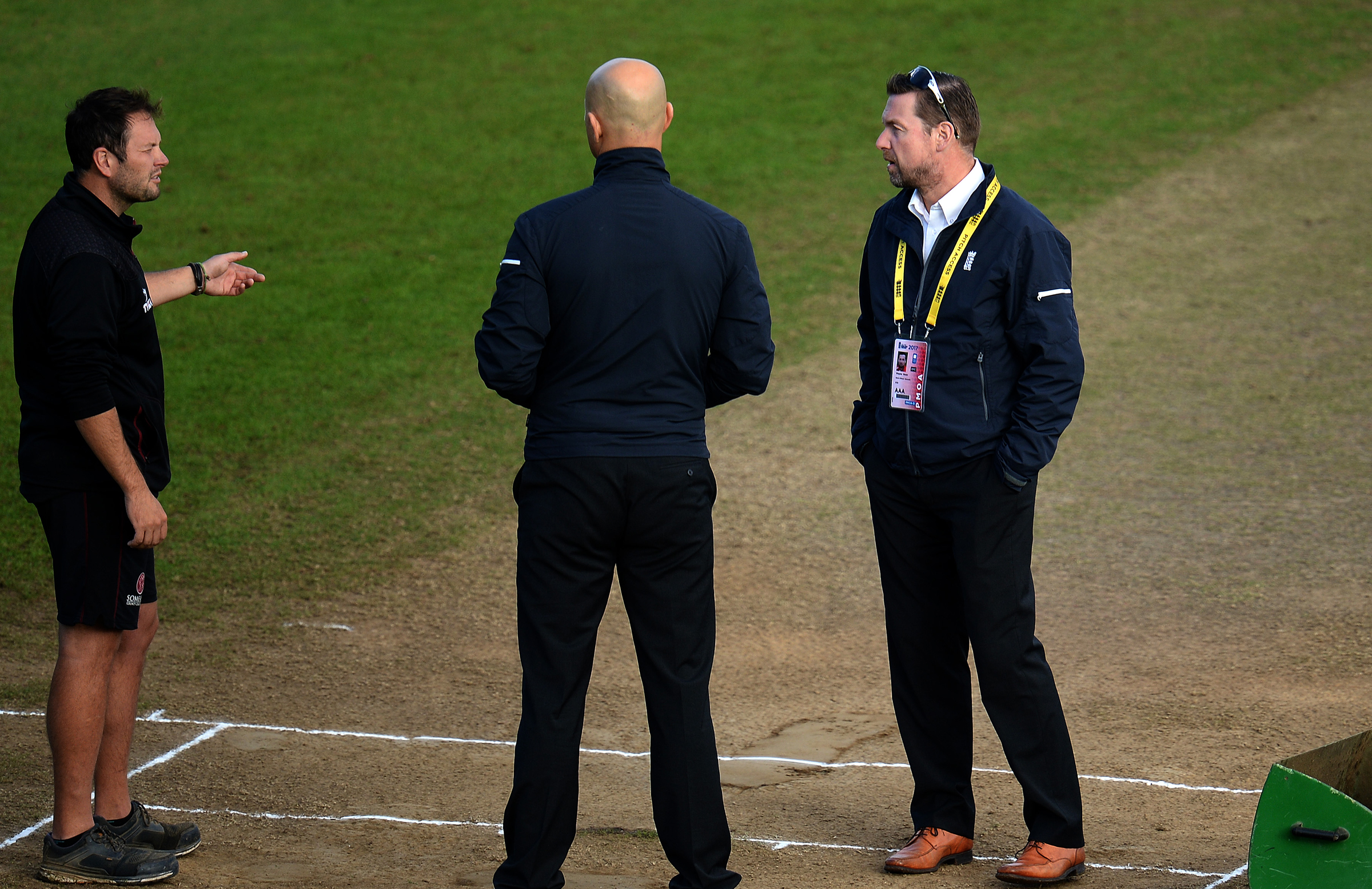Taunton groundsman Simon Lee (l) chats with umpire Alex Wharf (c) and the ECB's Wayne Noon (r) // Getty
