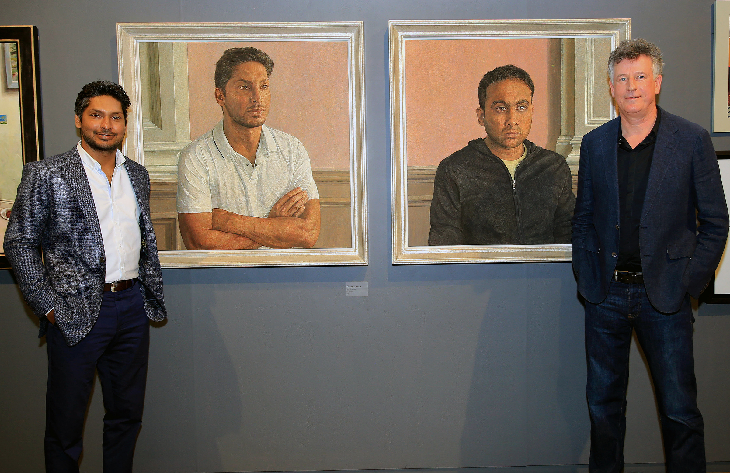 Subject and artist stand next to the portraits // MCC