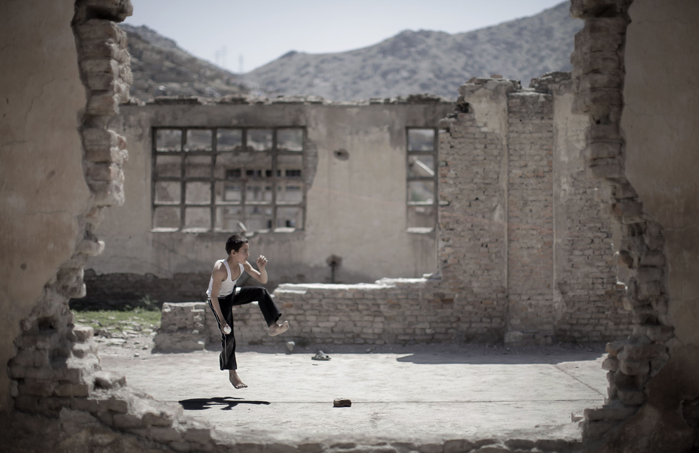 A child plays in the ruins of a compound on the outskirts of Kabul // Getty