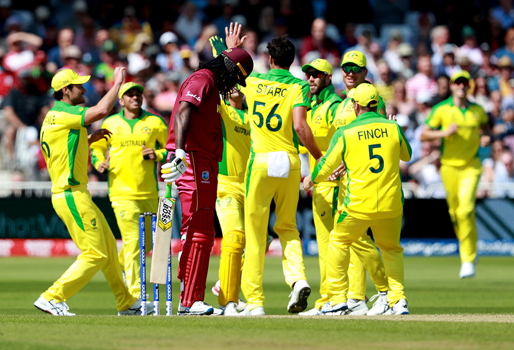 Starc and his Australian teammates celebrate the wicket of Chris Gayle // Getty