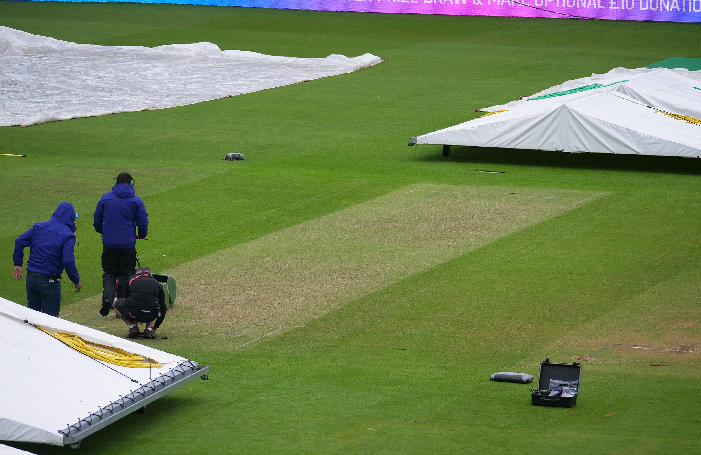 Ground staff take advantage of a break in the rain on Tuesday