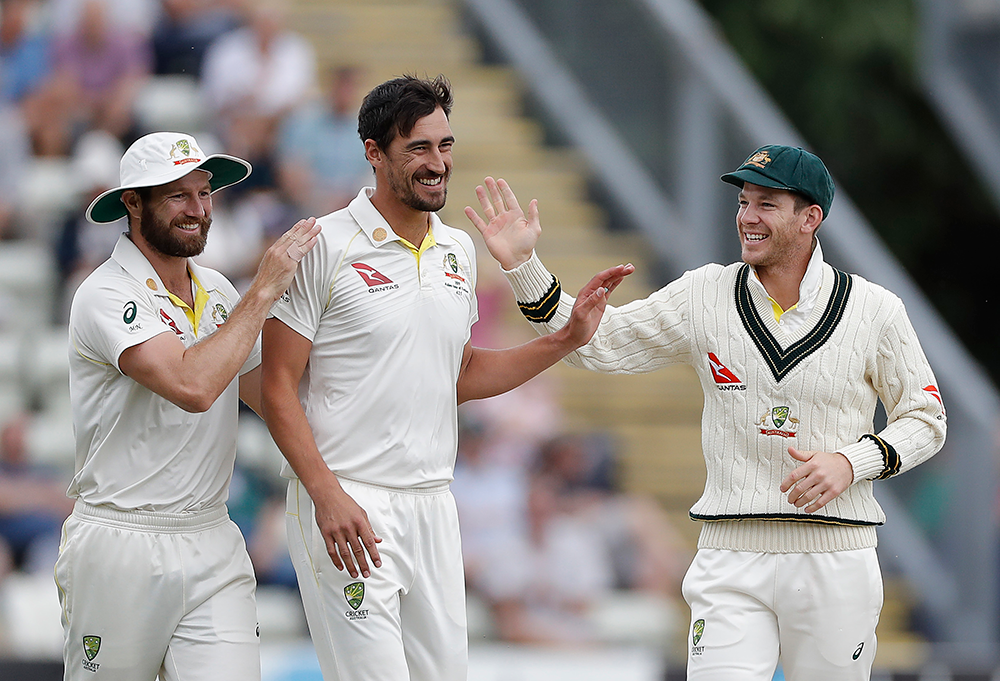 Paine, the out-fielder, celebrates a wicket with Mitchell Starc and Michael Neser // Getty