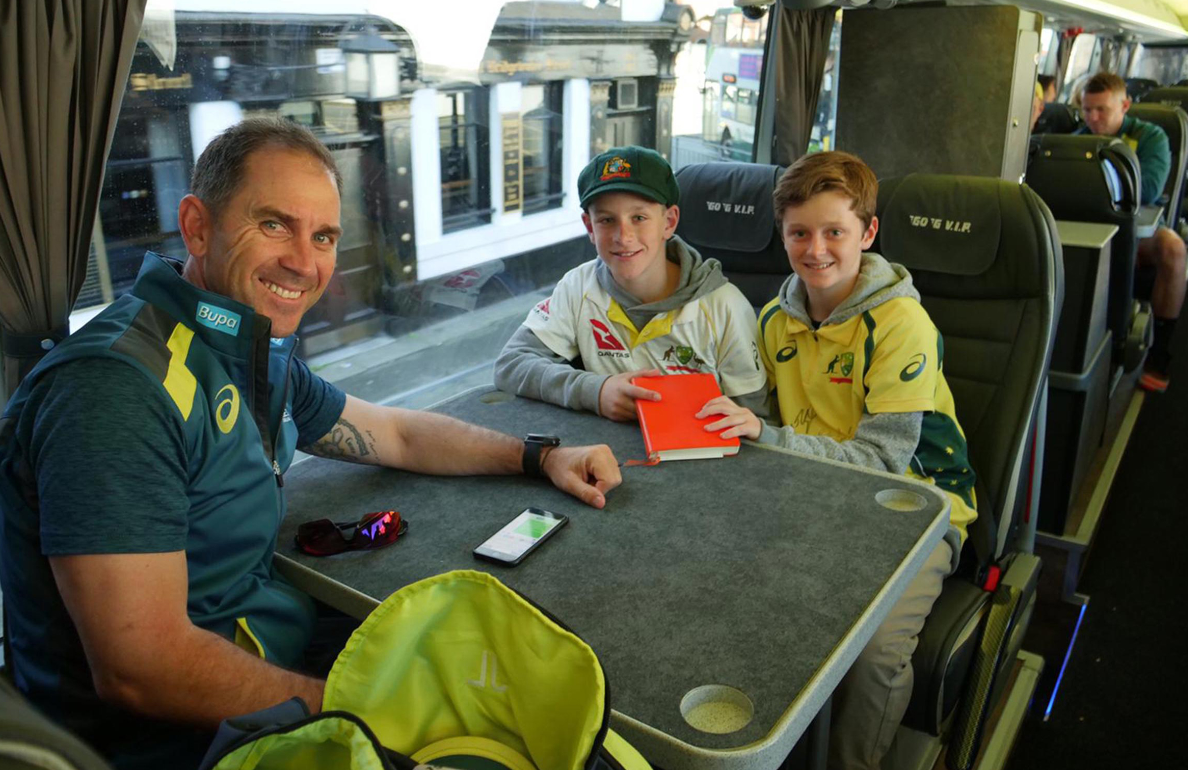 Max and his brother ride on the team bus with Justin Langer // supplied