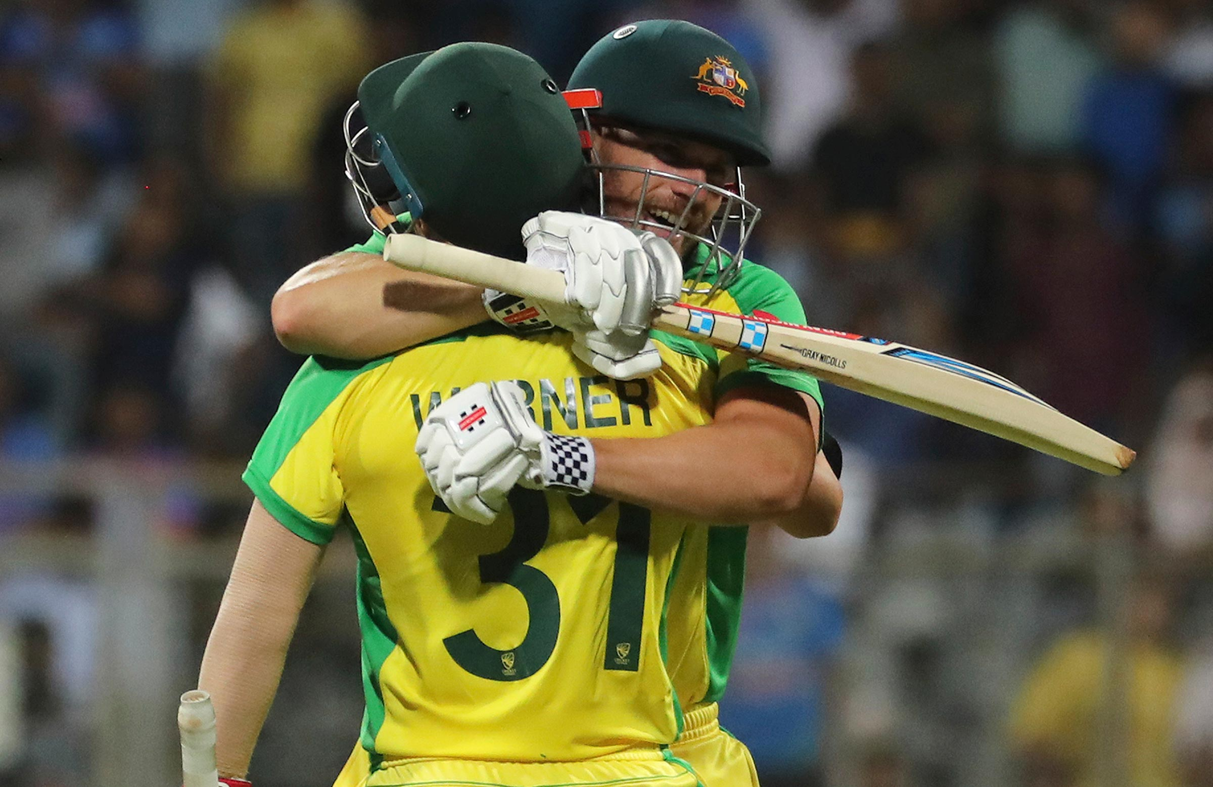 Finch and Warner embrace as the runs pile up // AAP